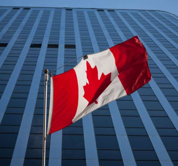Canadian-flag-in-front-of-a-business-building-in-Ottawa-Ontario-Canada.-Ottawa-is-the-capital-city-of-Canada-and-one-of-the-main-economic-1-min